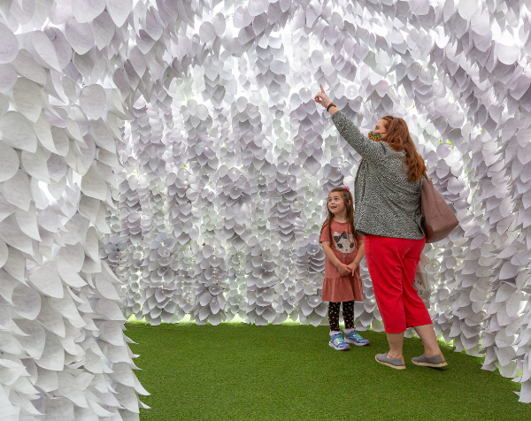 The image shows a mother and her young daughter inside the Breathing Room sculpture which is a sensory light tunnel made of white paper cones.