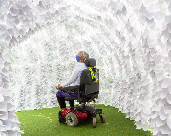 A woman in a wheelchair looks up inside the breathing room sculpture, surrounded by white paper cones