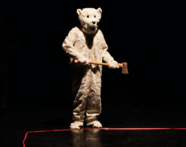 An actor wears a full polar bear costume on stage, holding an axe.